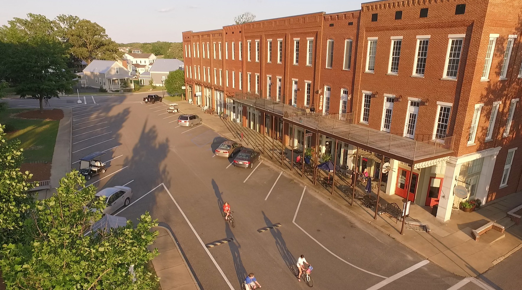 Photo of town square building with cars and bicyclists